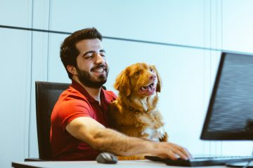 Man with big smile and dog on his lapse sitting behind computer